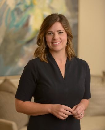 Smiling certified financial planner beth moody in a black dress stands with clasped hands