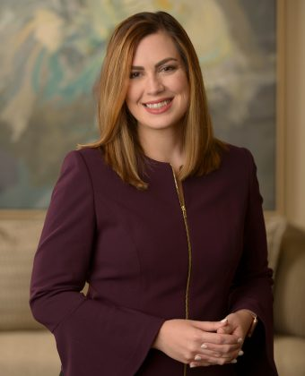 certified financial planner Callie Jowers wears maroon and gold zipper dress with hands clasped together, posing for professional photo in an office