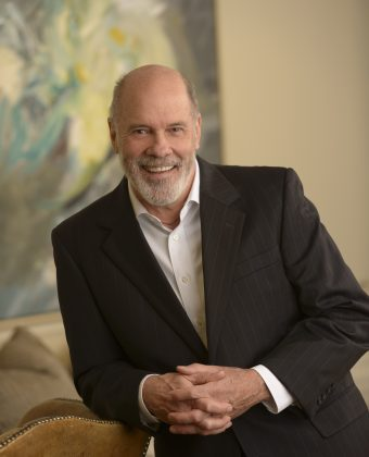 Certified public accountant Greg Weyandt wears a black jacket while leaning on a brown armchair