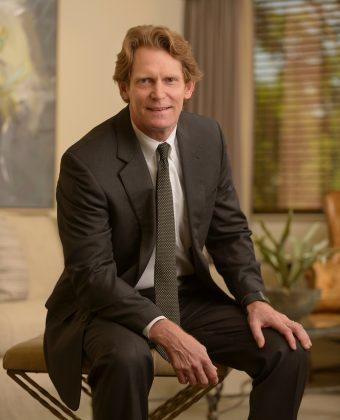 Certified public accountant Hugh smith wears a grey suit and leans forward while sitting on beige ottoman in an office