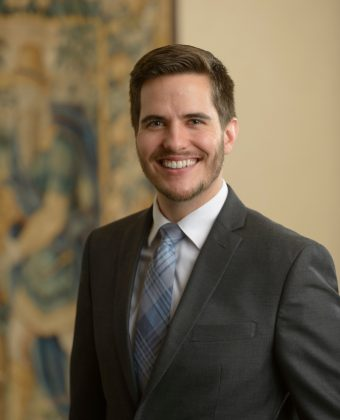 certified financial planner Justin Davenport smiles for portraits in an office while wearing a grey jacket and blue patterned tie