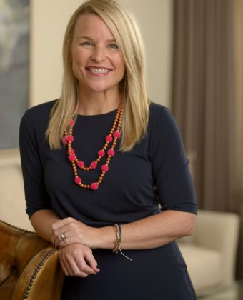 Standing Lauren Wright wears navy dress and orange necklace while leaning on a brown leather armchair in office