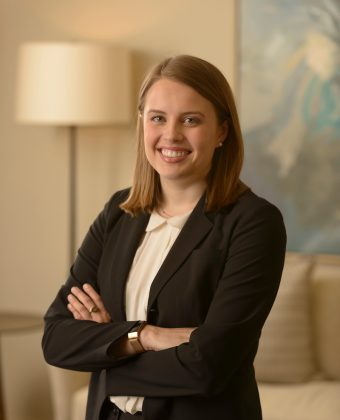 certified financial planner Maggie Elliot wears a black jacket and crosses arms while taking professional photo in office