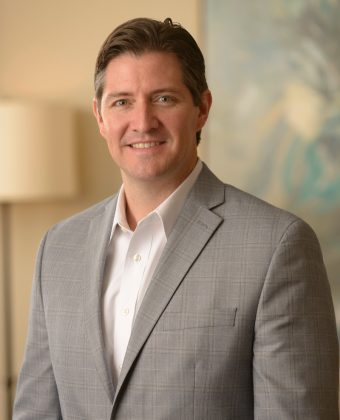 certified financial planner Marshall Clay wears a gray jacket and white shirt while posing for professional photo in office