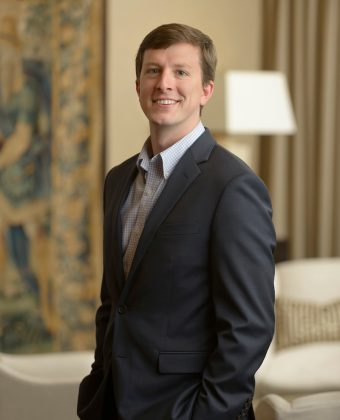 certified financial planner Matt Savela wears gray jacket while turning for professional photo in office