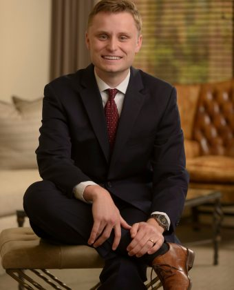 certified financial planner Reagan White wears black suit and red tie while sitting on beige ottoman in an office
