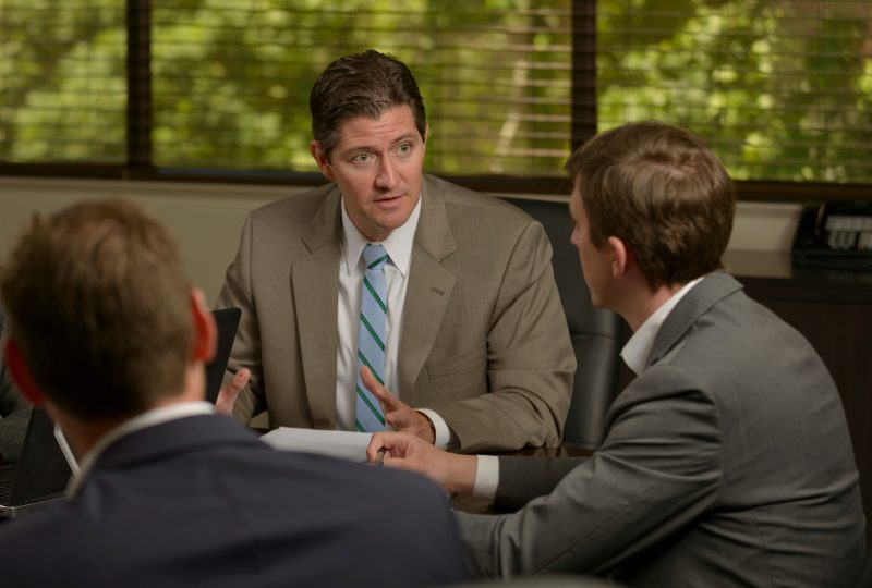 Three business men wearing suits discuss at a conference table