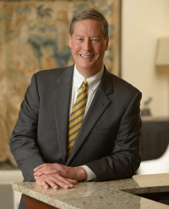 certified financial planner Woodard Peay poses in grey suit and yellow tie over granite countertop